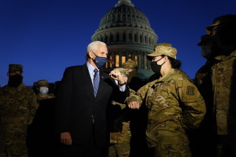 Vice President Mike Pence elbow bumps with a member of the National Guard as he speaks to troops outside the US Capitol on Thursday evening.