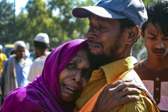 'They are taking us forcefully': a Rohingya man comforts a refugee woman as they are relocated to Bhashan Char.
