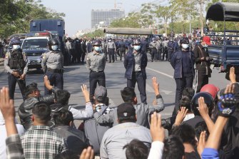 Protesters sit on a road blocked by police as they flash a three-fingered salute, a symbol of resistance, during a protest in Mandalay.