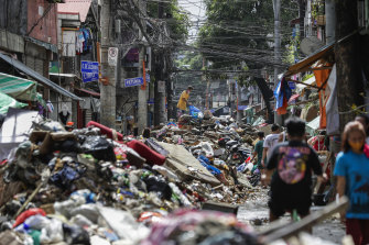 Residents climb over piles of debris washed in floodwaters from typhoon Vamco in Marikina, Philippines.