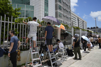 Reporters waiting outside Apple Daily on Thursday morning as police combed through files inside.