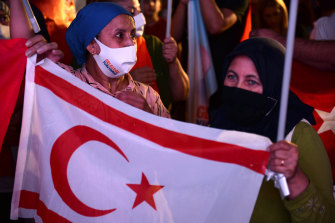 Supporters of the newly elected Turkish Cypriot leader hold the breakaway region's flag while celebrating the election results in the Turkish occupied area in the north part of the divided capital Nicosia.