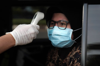 A motorist has her temperature checked at a checkpoint in Jakarta, Indonesia, on Friday.