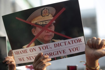 A Burmese protester living in Thailand holds a picture of Myanmar military chief Min Aung Hlaing.