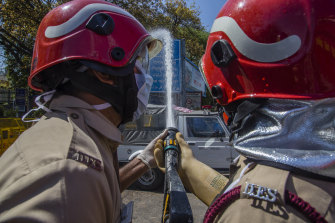 Indian firefighters disinfect a sealed area outside an Islamic seminary in the Nizamuddin neighbourhood of Delhi, after a 36-hour-long operation to evacuate 2631 Muslims to hospitals for quarantine earlier this month.