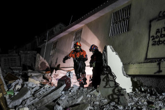 Mexican firefighters search rubble in the town of Les Cayes.
