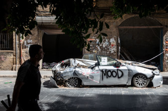 A man walks past a car that was destroyed in the blast it Beirut's port on August 4.