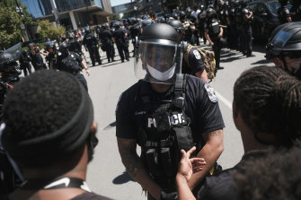 """Police speak with protesters outside the Louisville Court House in Kentucky earlier this month. Members of a self-described """"patriot militia"""" clashed with people protesting against the killing of Breonna Taylor."""