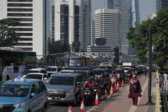 Motorcyclists wait alongside vehicles in traffic in the business district in Jakarta during a partial coronavirus lockdown.