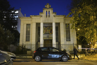 A woman walks past the Greek Orthodox church after a priest was shot.
