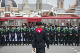 Police officers wearing face masks stand in line, protecting the area surrounding the Grand Palace during a protest in Bangkok last month.