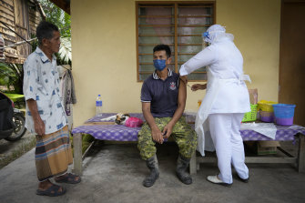 A nurse administers a Pfizer vaccine to a farmer outside his home in Sabab Bernam, a rural area in the state of Selangor.