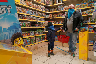 Rihan, 5, leads his father Erdem while shopping in a toy store that was opening for the first time since March, in Berlin.