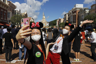 Visitors wear face masks at Hong Kong Disneyland last month.