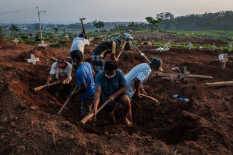 Grave diggers conduct a burial at Jatisari public cemetery, reserved for suspected COVID-19 victims, in Semarang, Central Java.