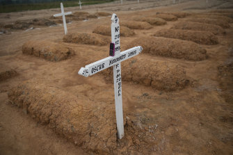 A gravedigger's phone rests on a cross marking the grave of a COVID-19 victim at a new cemetery for victims of the pandemic on the outskirts of Pucallpa, Peru.