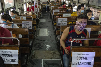 Commuters sit on a bus with seats spaced to observe social distancing in Manila on Monday.