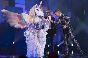 The Masked Singer contestant Unicorn with the show's host Osher Günsberg.