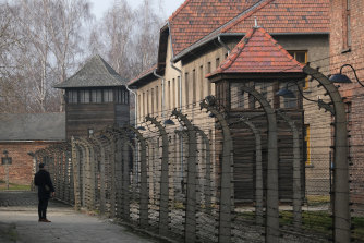 A visitor walks behind the barbed wire of the former Auschwitz-Birkenau concentration camp.