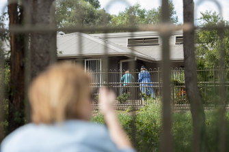 Mary Watson waves to her mother Alice Bacon, 93, who currently has coronavirus at Newmarch House.
