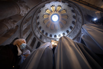 A masked woman attends Easter Sunday Mass led by Latin Patriarch of Jerusalem Pierbattista Pizzaballa at the Church of the Holy Sepulchre in Jerusalem.