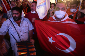 Supporters of the newly-elected Turkish Cypriot leader Ersin Tatar hold a Turkish flag and celebrate winning, in the Turkish occupied area in the north part of the divided capital Nicosia, Cyprus on Sunday.