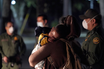 A migrant child sleeps on the shoulder of a woman at an intake area after turning themselves in upon crossing the US-Mexico border in the early hours of Wednesday.