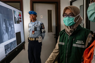 An Indonesian health official monitors international passengers as they pass a thermal scanner monitor in Yogyakarta.