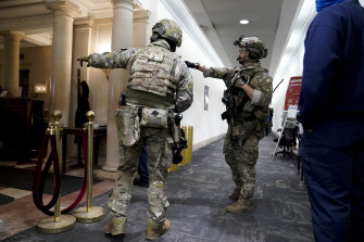 Members of the Federal Bureau of Investigation swat team patrol the halls after the capitol Hill riots.