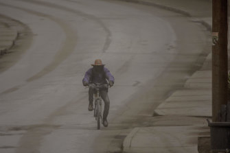 A man rides his bicycle along a road as ash falls from the erupting volcano.