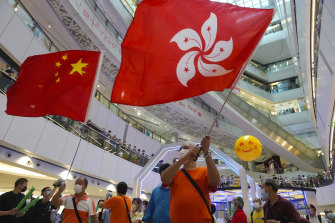 People wave a Hong Kong flag and a Chinese national flag as they watch Olympics events at a shopping mall in Hong Kong on Friday, July 30.