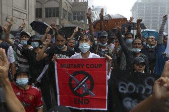 Pengunjuk rasa anti kudeta dalam hujan di Pabedan, Myanmar, pada hari Jumat. Orang-orang terus berdemonstrasi menentang kudeta militer meskipun ada tindakan keras berdarah yang merenggut ratusan nyawa.