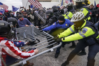 Trump supporters and police in a tug of war outside the US Capitol on January 6.