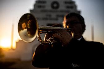 Afghanistan war veteran Duncan Clements plays his bugle at dawn at the Parkes War Memorial in 2020.