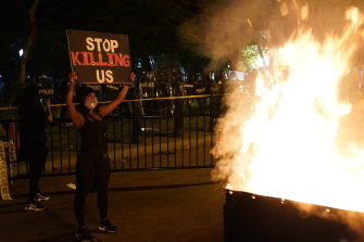 A fire burns in a dumpster near the White House as demonstrators protest the death of George Floyd.