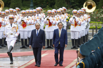 Japanese Prime Minister Yoshihide Suga, right, and his Vietnamese counterpart Nguyen Xuan Phuc, left, attend a welcoming ceremony at the Presidential Palace in Hanoi, Vietnam.