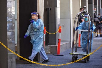 Staff in protective gear help transfer guests from the Holiday Inn on Flinders Lane on Tuesday.
