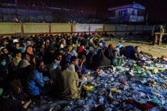 Afghan refugees crouch in a group as British military secure the perimeter outside the Baron Hotel, near the Abbey Gate, in Kabul, Afghanistan.