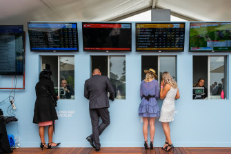Racegoers place bets at the Birdcage during Stakes Day.