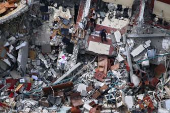 A man inspects the destroyed building that housed the offices of The Associated Press and other media in Gaza City.