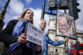 Protesters hold placards near Parliament Square, in London, on the day Dominic Cummings, the volatile advisor who until late last year was British Prime Minister Boris Johnson's most powerful and trusted aide, appeared at a commitee hearing.