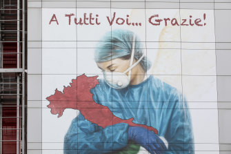 A mural on the side of a building in Lombardy shows a medical worker cradling Italy.