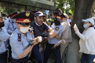 Police wearing a face masks to protect against coronavirus, detain a protester during a protest in Almaty, Kazakhstan last month.