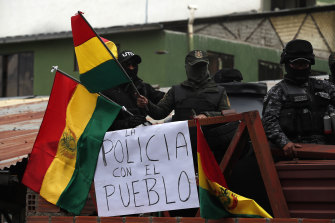"""Police against the re-election of President Evo Morales stand on the rooftop of a police station just meters away from the presidential palace waving national flags, near a sign that reads in Spanish: """"The police is with the people""""."""