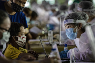 A medical worker interviews a child queuing for a free COVID-19 swab in Manila.