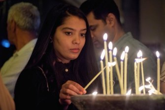 An Easter worshipper lights a candle at St Patrick's Cathedral