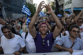 Anti-vaccine protesters shout slogans as they march to the parliament, in Athens, on Saturday.