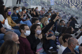 "Concert-goers in Tel Aviv enjoy a performance at a soccer stadium after presenting proof of vaccination via their ""green passport"" - available on an app or as a printed tag."