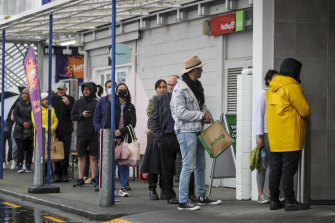 Shoppers line up to enter a supermarket in Auckland on Tuesday. The city is going into a snap seven-day lockdown.