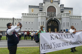 """rotesters hold a sign saying """"Kamala Mind Your Own Business"""" as the motorcade of Vice-President Kamala Harris travels to the National Palace, Monday, June 7, 2021, in Guatemala City."""